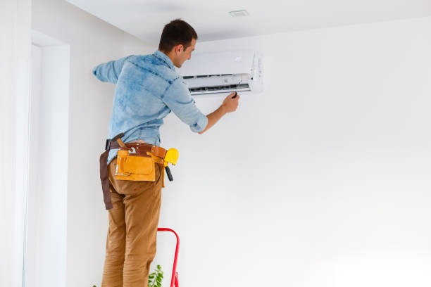 Worker installs grid on the air conditioner in the new apartment stock photo