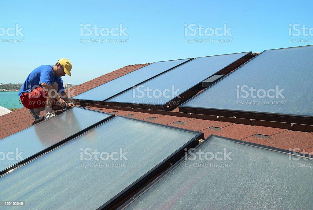 Worker installs solar panels stock photo