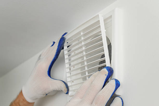 Worker installs ventilation grille. stock photo