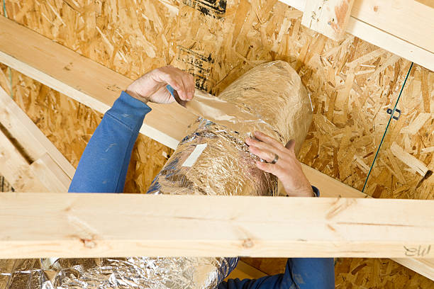 Worker Insulating an Attic Vent Duct with Aluminum Foil Tape stock photo