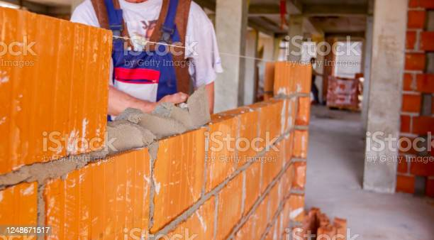 Worker is building wall with red blocks and mortar picture id1248671517?b=1&k=6&m=1248671517&s=612x612&h=x5  vqzkqmth3xmgalhuxbxrjsoc6djtyllwizabm9m=