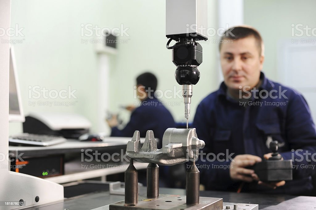 Worker is checking quality of new machine part stock photo