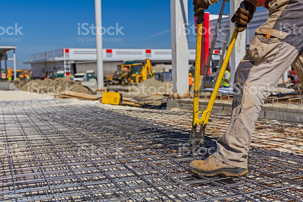 Worker is cutting rebar with scissors for reinforcement bars. stock photo