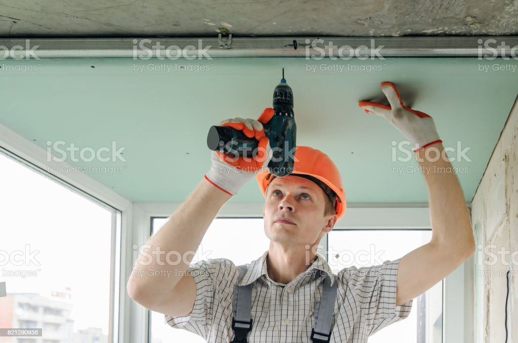 Worker is fixing the drywall. stock photo