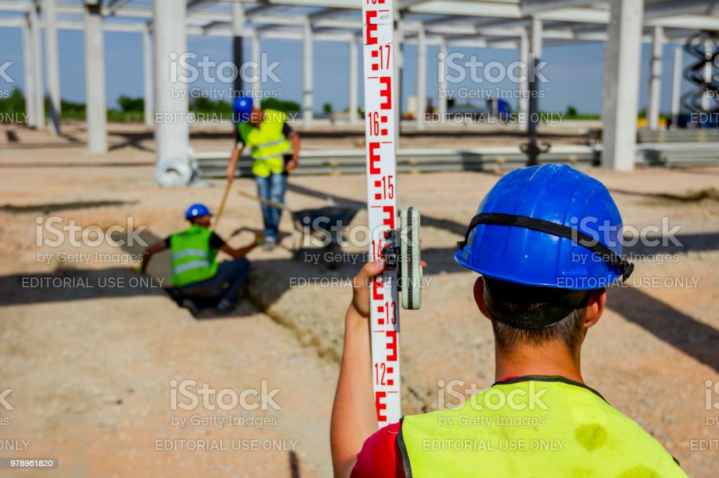 Worker is holding leveling rod to measuring level on construction site stock photo