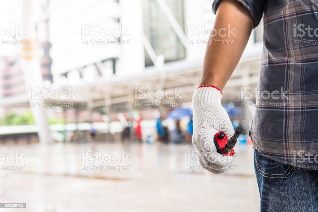 Trabalhador é com a red walky talky pela mão direita que usar algodão luva - foto de acervo
