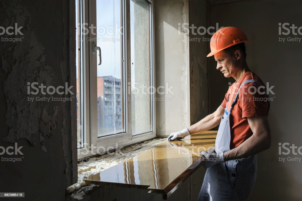 Worker is installing a window sill. stock photo