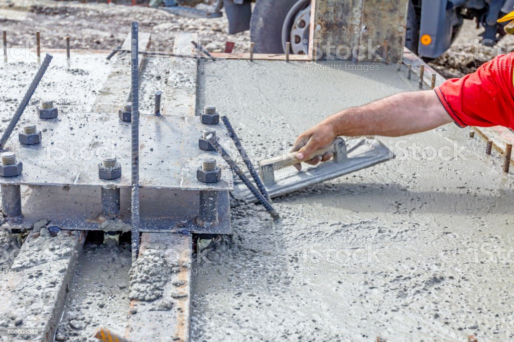 Worker is leveling concrete after pouring stock photo