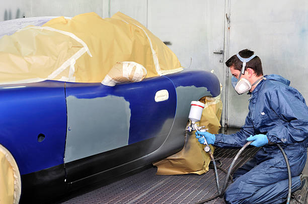 worker is professionally painting a vehicle royal blue - auto body repair stock photos and pictures