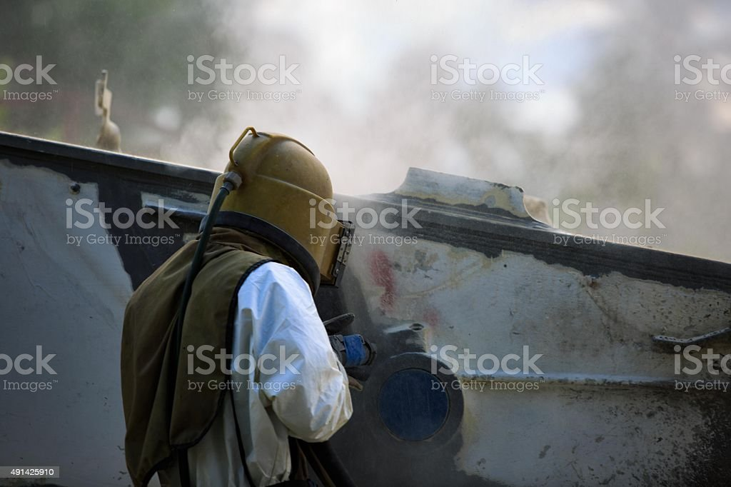 Worker is remove paint by air pressure sand blasting stock photo