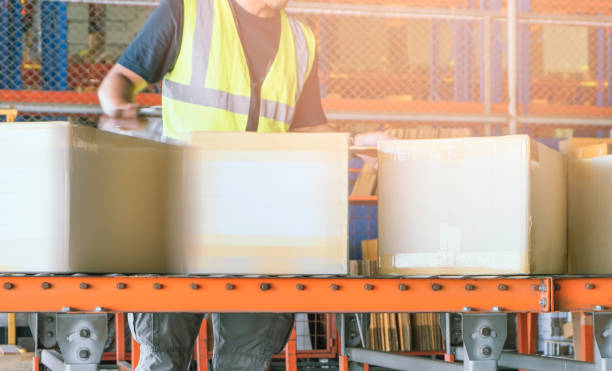 Worker is sorting package boxes on conveyor belt, cartons, cardboard boxes, delivering shipment parcels, Worker is sorting package boxes on conveyor belt, cartons, cardboard boxes, delivering shipment parcels, distribution center stock pictures, royalty-free photos & images