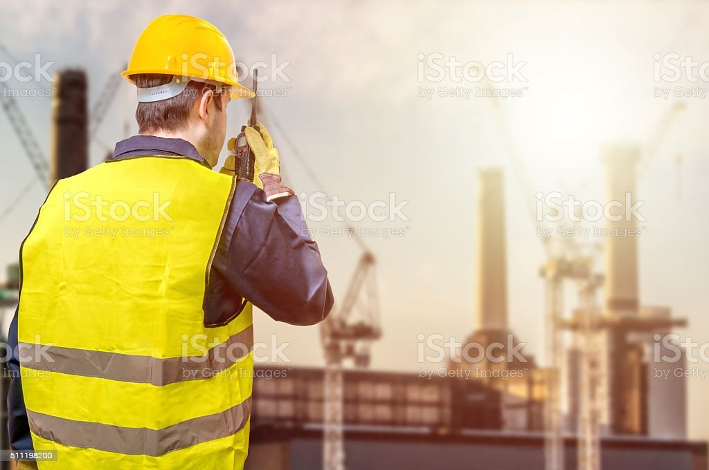 Worker is using radio and crane site during sunset, construction stock photo