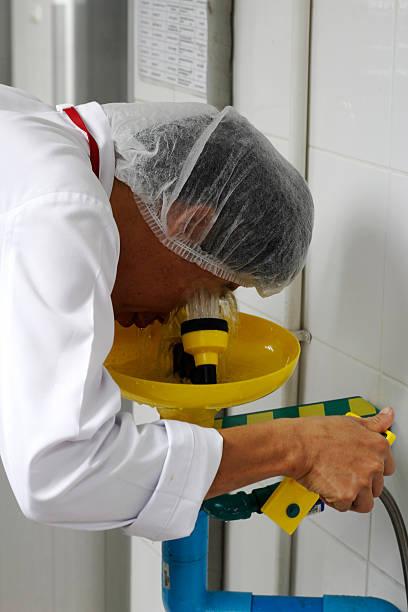 pracownik korzysta z prysznicem oczy umyć - dworzec zdjęcia i obrazy z banku zdjęć