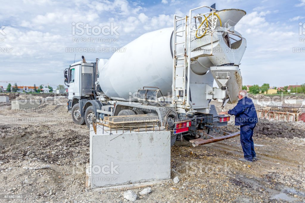 Worker is washing, packing for traffic his concrete mixer. stock photo
