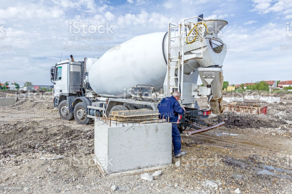 Worker is washing, packing for traffic his concrete mixer stock photo