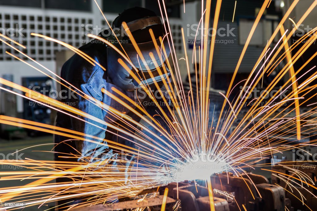 worker is welding assembly automotive part in car factory stock photo