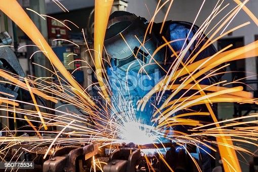 istock Worker is welding automotive part in car factory 950773534