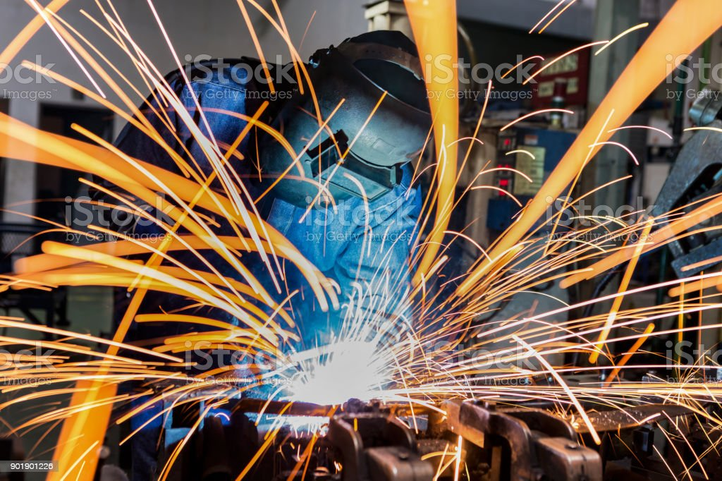 Worker is welding in car factory stock photo