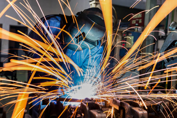 Worker is welding in car factory Worker is welding in car factory metalwork stock pictures, royalty-free photos & images