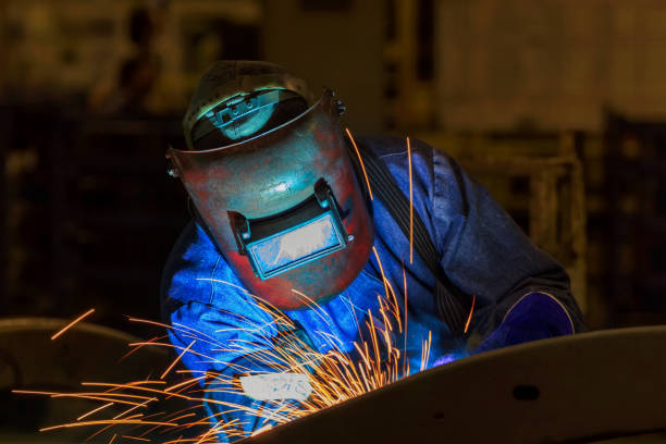 worker is welding metal part in car factory worker is welding metal part in car factory naval base stock pictures, royalty-free photos & images