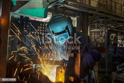 Worker is welding metal part in factory