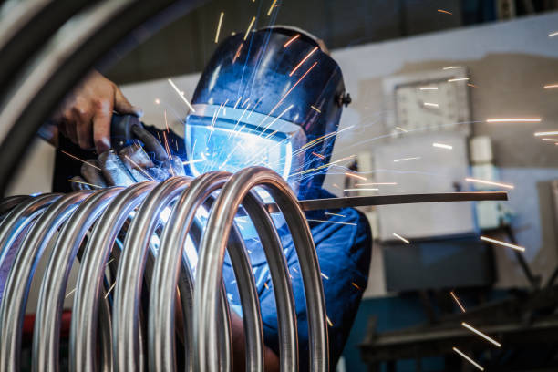 Worker is welding metal tubes. Details of the production process. metalwork stock pictures, royalty-free photos & images