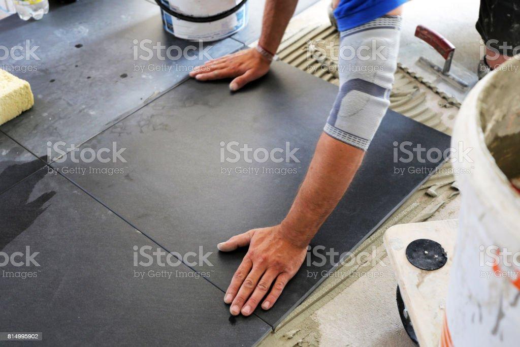 Arbeiter verlegen Bodenfliesen – Foto