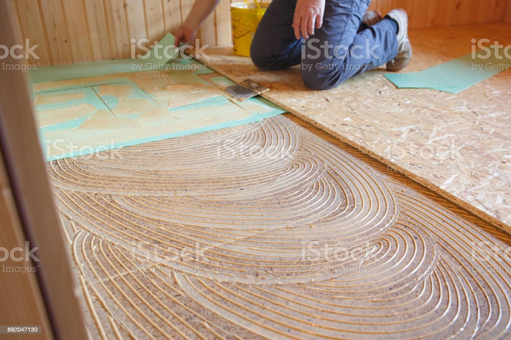 Worker laying insulation layer and spreading adhesive primer stock photo
