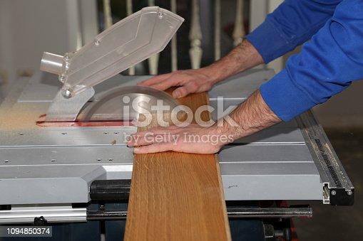 istock Worker laying parquet flooring. Worker installing wooden laminate flooring. 1094850374