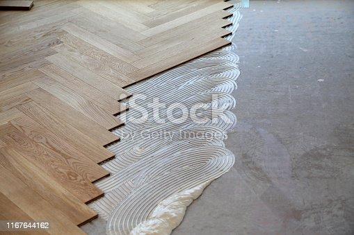 Worker laying parquet flooring. Worker installing wooden laminate flooring.