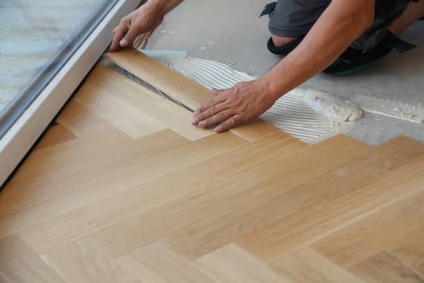 工人鋪著鑲木地板。工人安裝木制層壓地板 - 大廈樓層 個照片及圖片檔