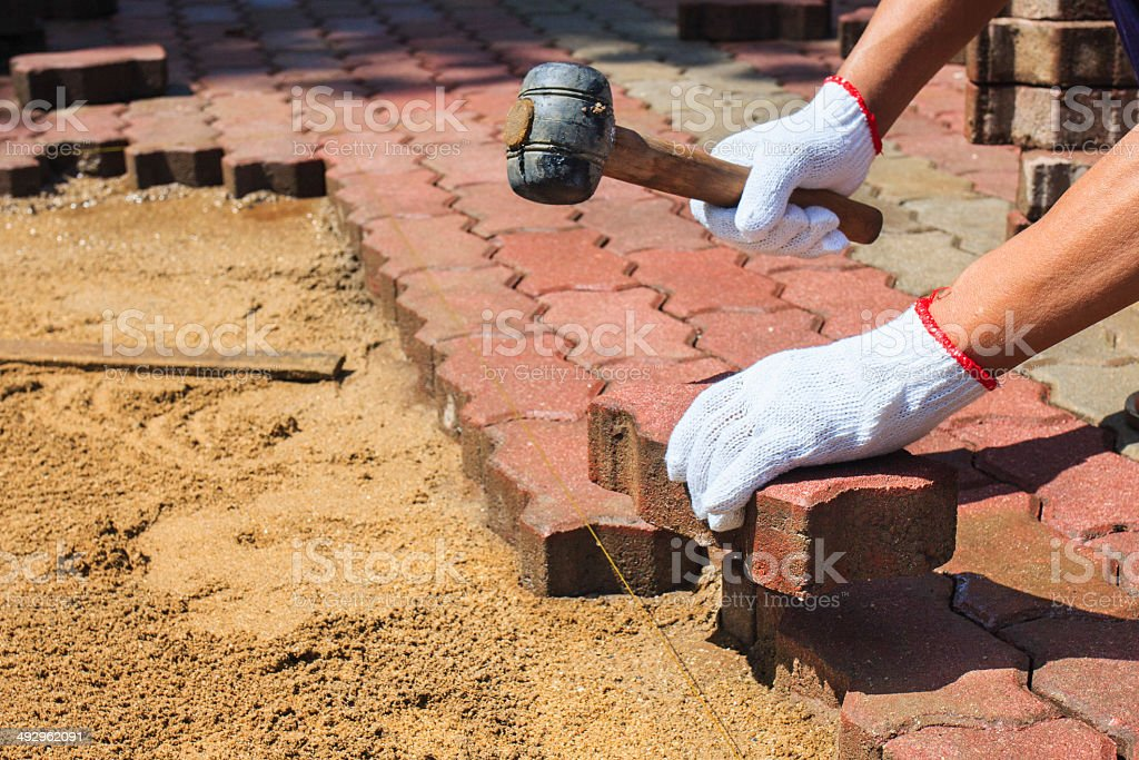 worker laying red concrete paving blocks. stock photo
