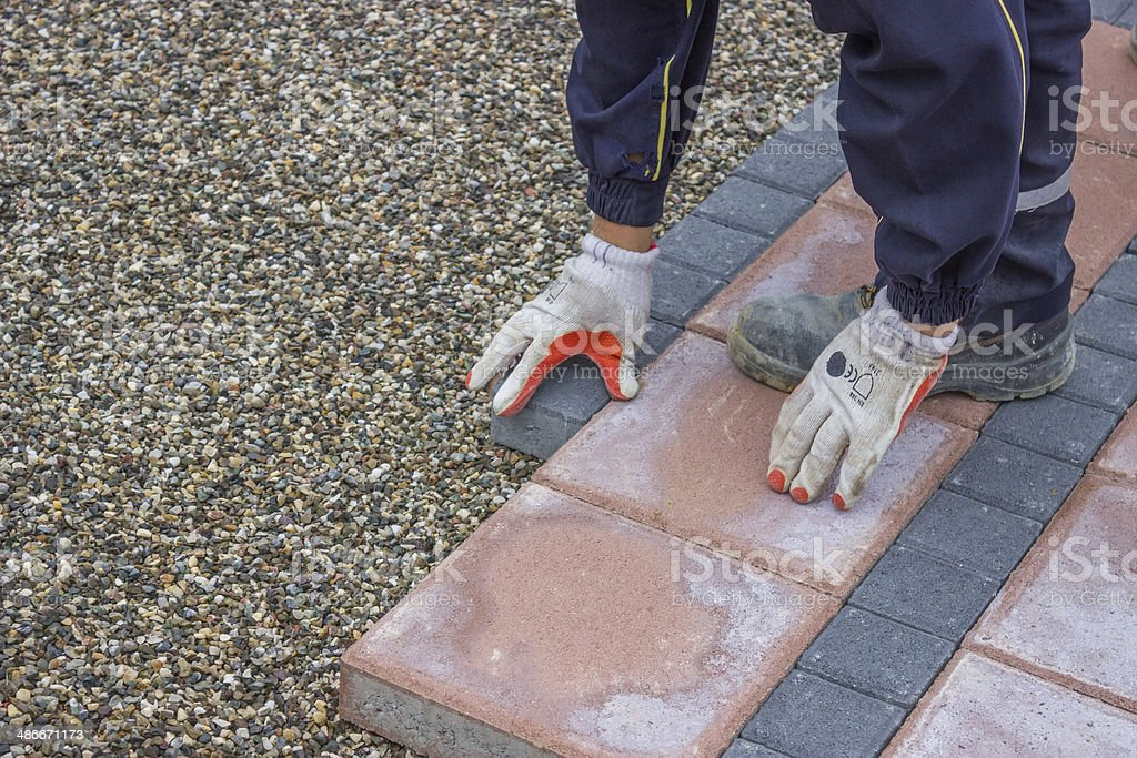 worker lays brick pavers along the sidewalk stock photo