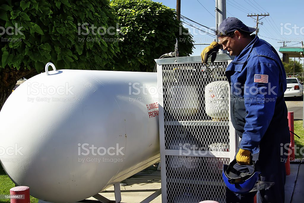 Worker leaning against natural gas tank cage stock photo