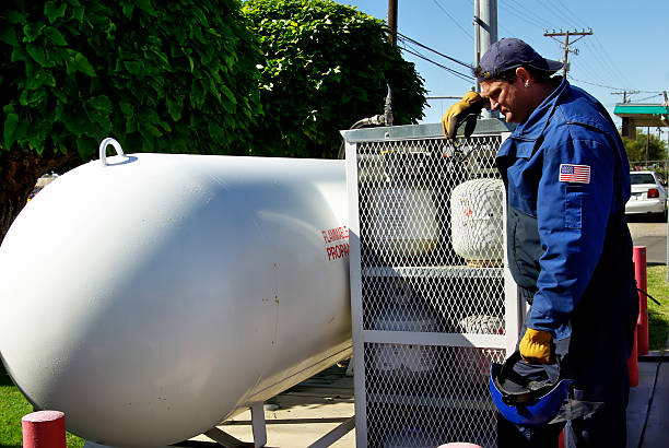 worker leaning against natural gas tank cage - mikefahl stock pictures, royalty-free photos & images