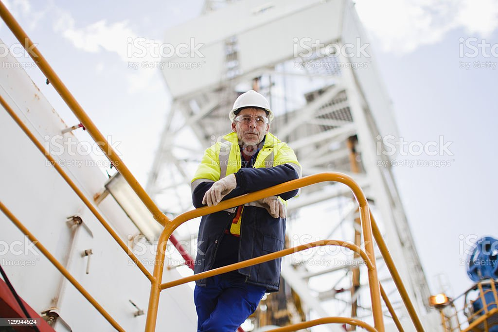 Worker leaning on railing of oil rig stock photo