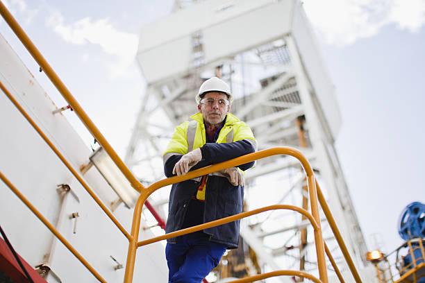 Trabalhador inclinada no parapeito da Plataforma Petrolífera - foto de acervo
