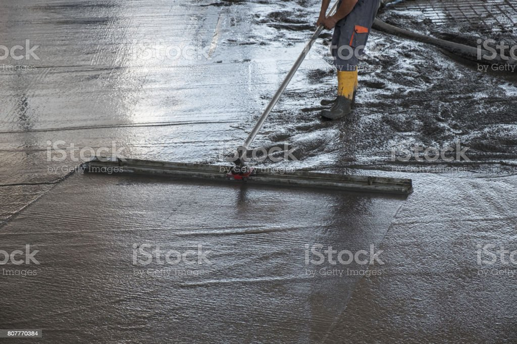 Worker leveling fresh poured concrete floor stock photo