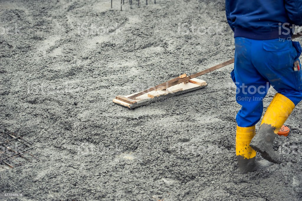 Worker leveling with wooden trowel the fresh poured concrete stock photo