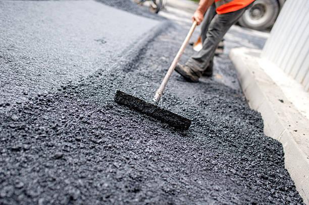 operaio livellamento fresca su una strada asfaltata costruzione sito - asfalto foto e immagini stock