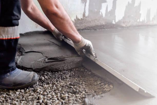 il lavoratore pianta una malta cementizia a pavimento. piano uguale. riparazione della casa. - calcestruzzo foto e immagini stock