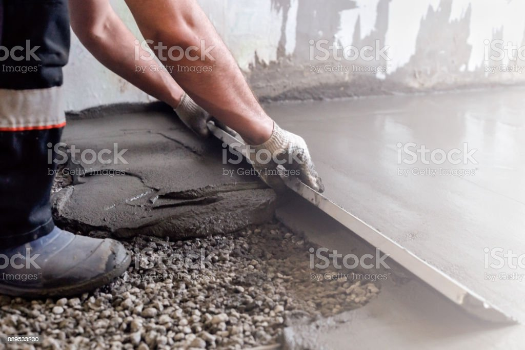 Worker levels a floor cement mortar. Equal floor. Repair of the house. stock photo