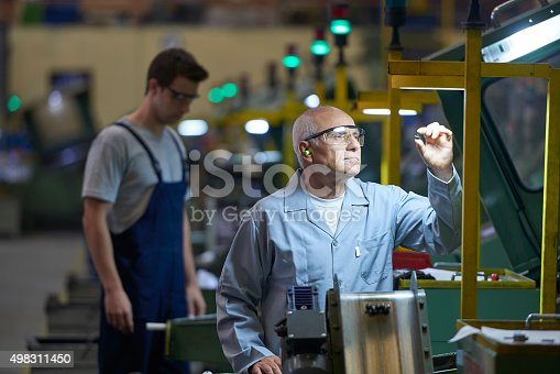 Worker checking product in bolt factory