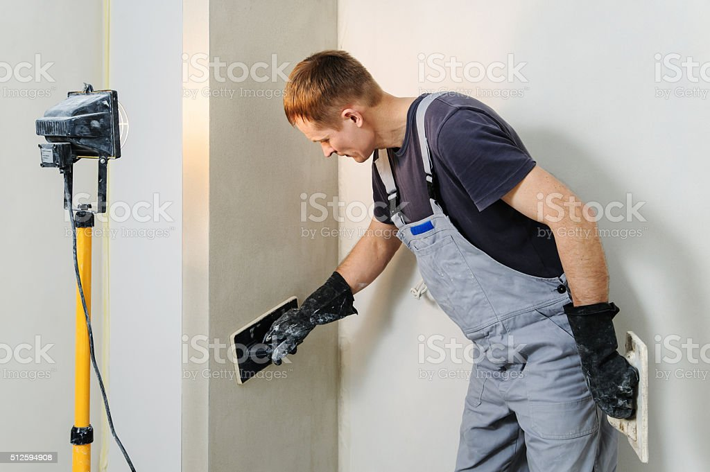 Worker makes final smoothing plaster on the wall. stock photo