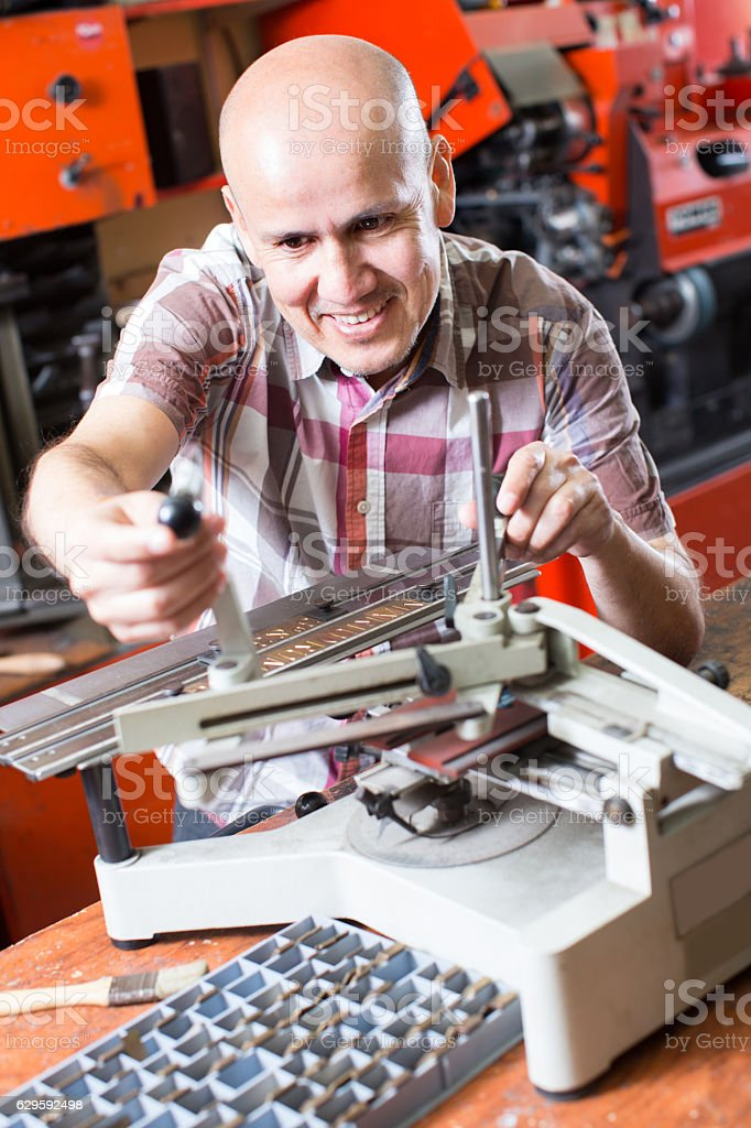 worker making nameboard stock photo