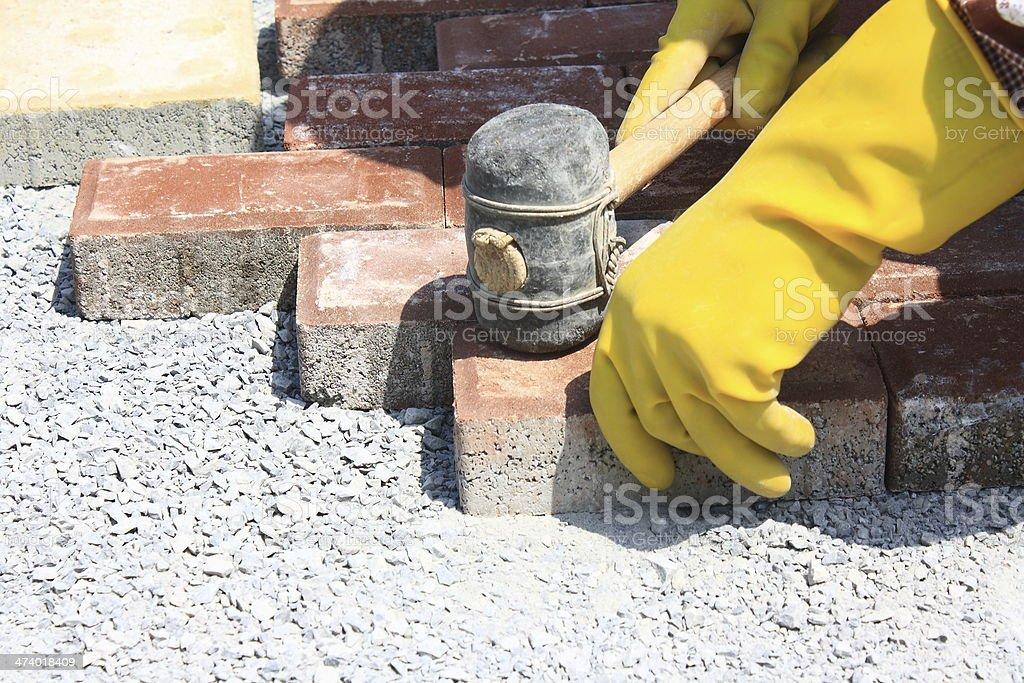 Worker making sidewalk pavement with stone blocks stock photo
