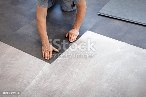 Worker making flooring with vinyl tiles