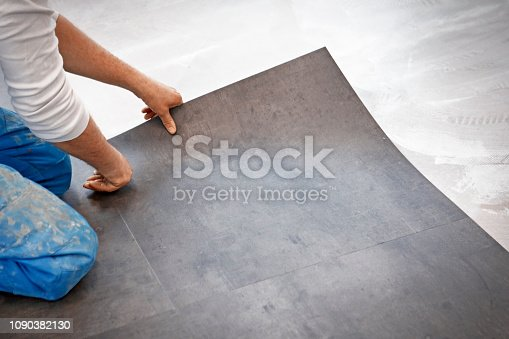 Worker making flooring with vinyl tiles