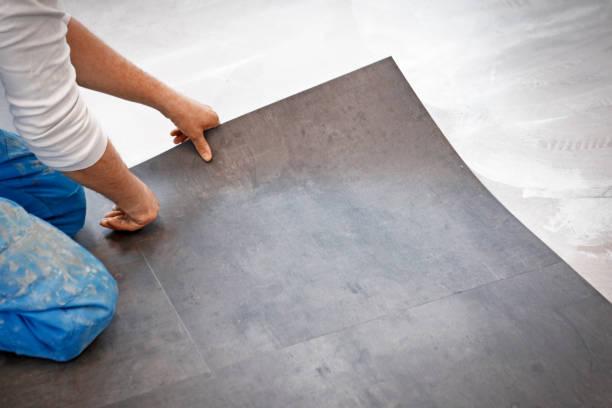 Worker making vinyl flooring Worker making flooring with vinyl tiles linoleum stock pictures, royalty-free photos & images