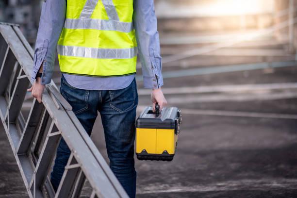 werknemer man het dragen van aluminium ladder en gereedschapskist - ladder stockfoto's en -beelden